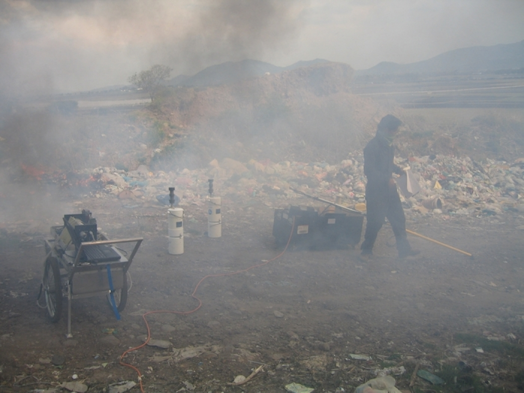 for air pollution trash is a burning problem climate central a field worker and the equipment used to measure emissions from burning trash near city as seen through a shroud of smoke click image to enlarge